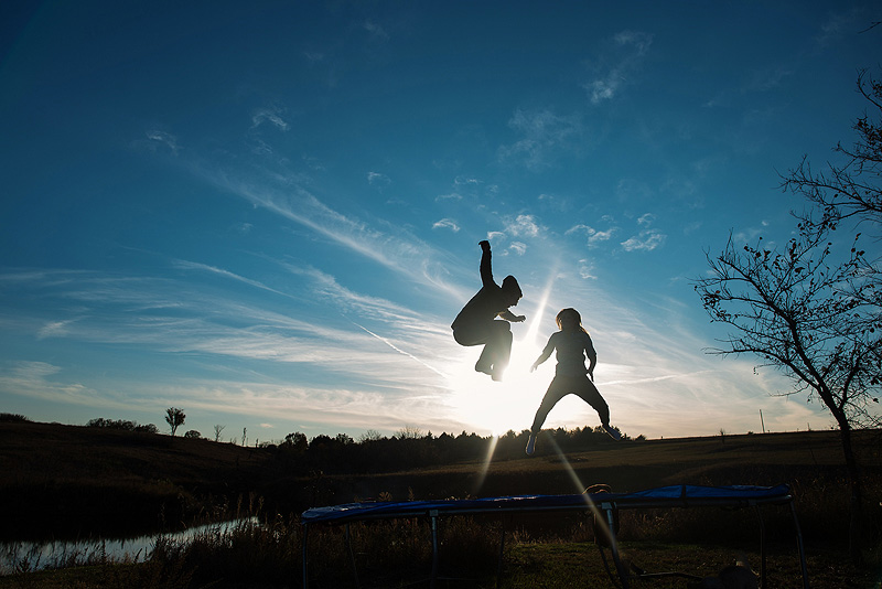 Copule jumping on the trampoline for their engagement photos.