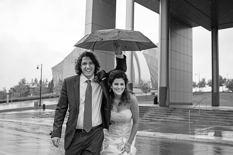 Bride and groom under a broken umbrella on their wedding day.