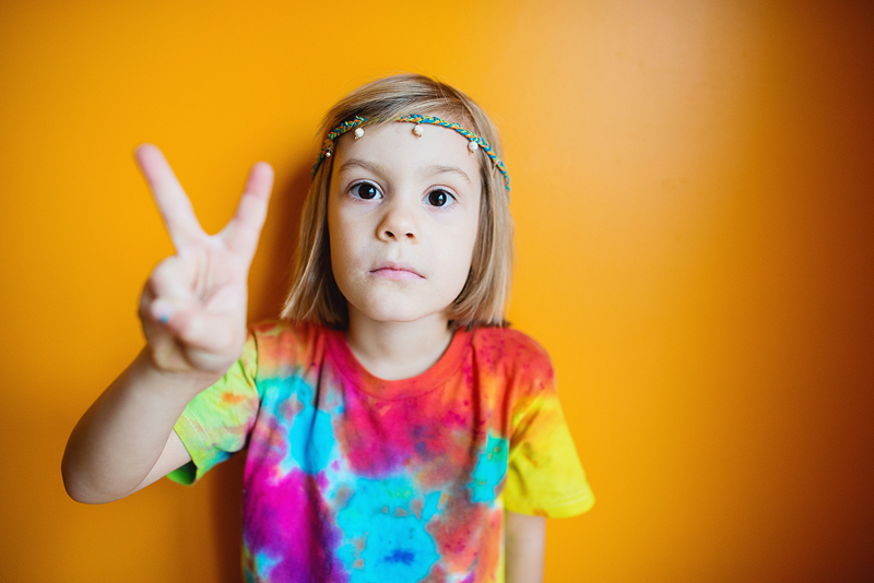 Girl in a tie dye shirt and a headband.