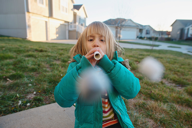 Girl shooting a marshmallow shooter.