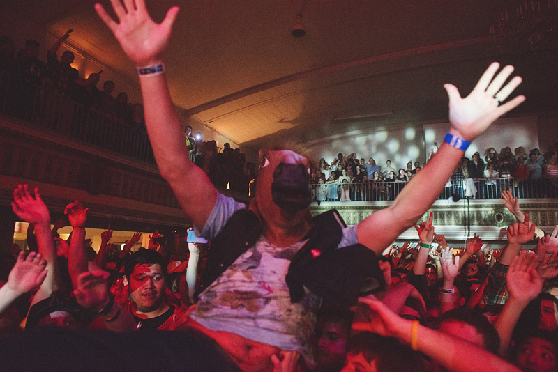 Crowd surfing with a horse head on.