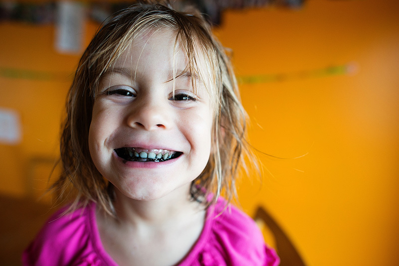 Smiling girl with icing in her teeth.