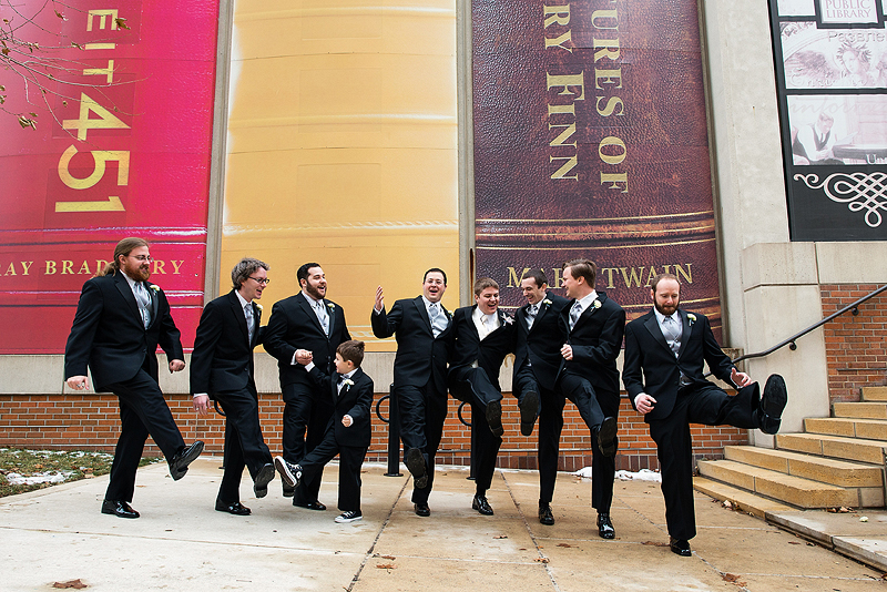 Groomsmen dancing in front of the library downtown Kansas City.