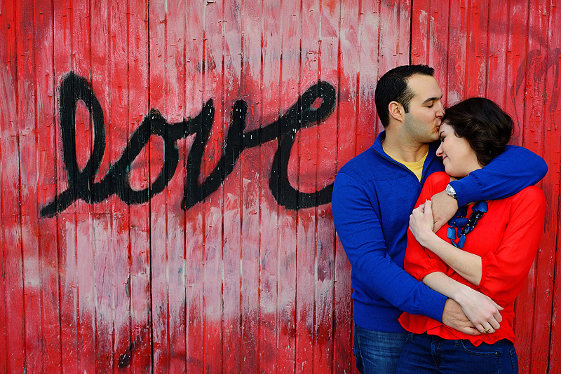 Couple kissing by the love wall on KU campus.