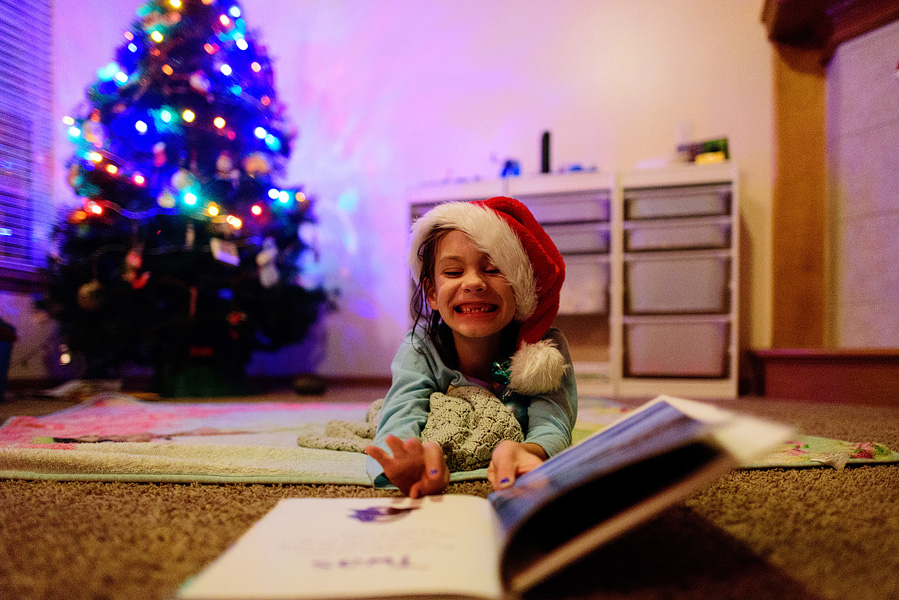 Excited girl reading the Night Before Christmas.