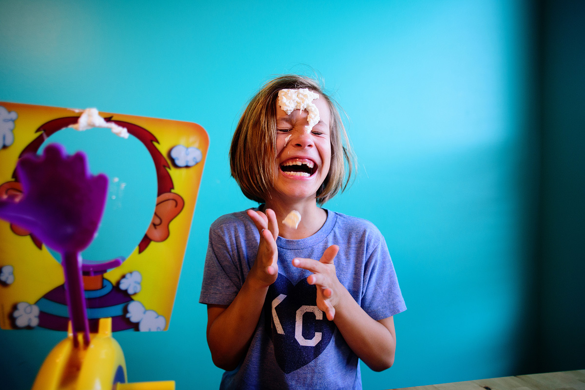 Laughing girl playing pie face